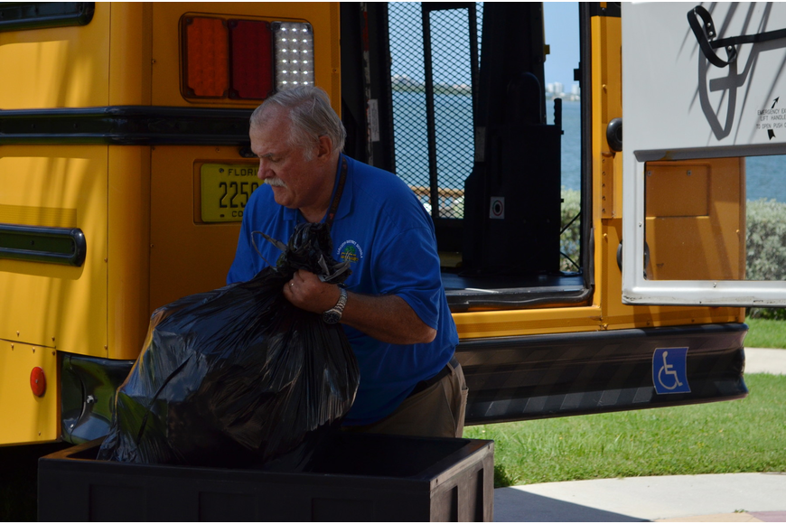 Bus driver Craig Taylor loads the backpacks into a school bus.