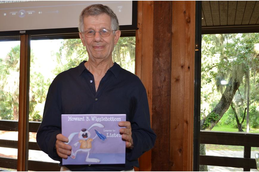 "Binkow displays the cover to his title ""Howard B. Wigglebottom Learns to Listen."""