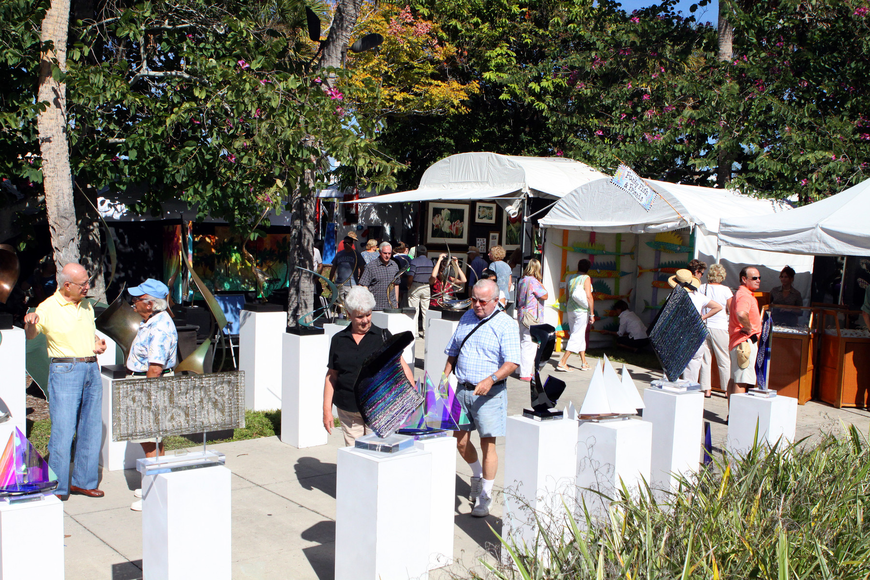 People walk around looking at pieces of art along St. Armands Circle during the 21st annual St. Armands Art Festival.
