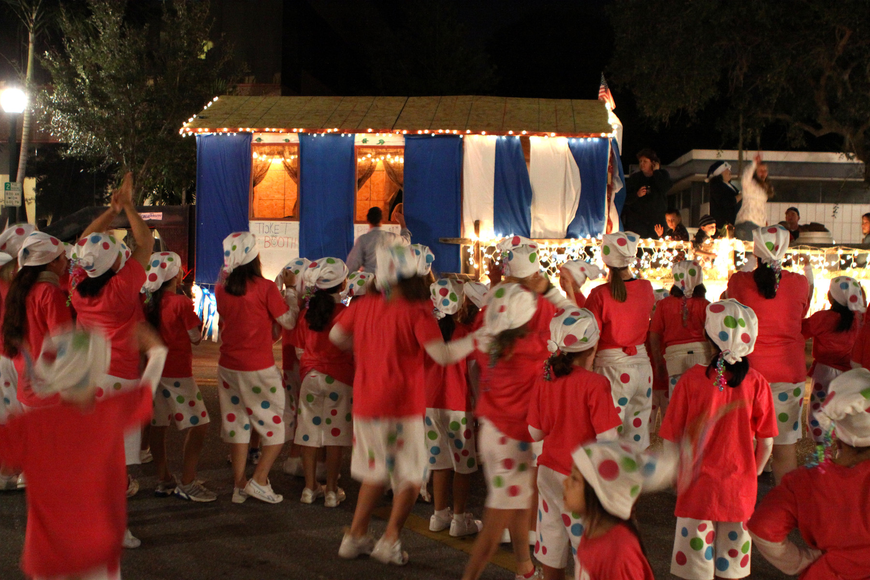 Kids from Jump Dance Company wave as other floats start going down Main street for the parade.