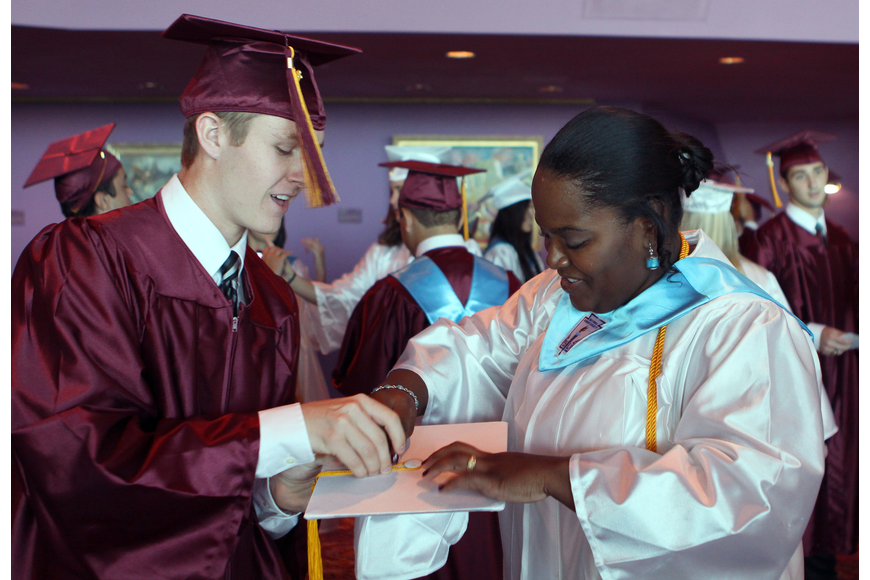 Tim McGrail tries to help Reyna St. Louis with her cap and tassel Friday, May 27 at the Van Wezel Performing Arts Hall.