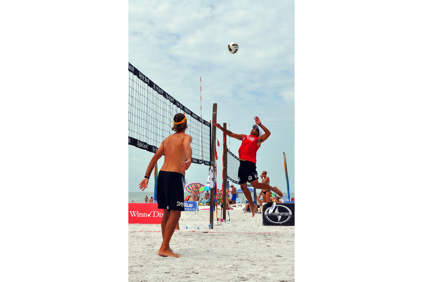 Adrian Carambula goes up to spike the ball as his teammate, Steve Grotowski, looks on during the Siesta Key Gulf Open, Saturday, July 9 at Siesta Key Beach.