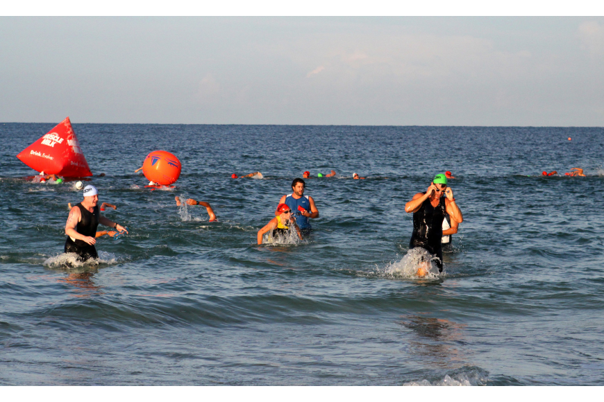 Participants make their way to shore after completing the swimming portion of the race Saturday, July 23 out at Siesta Key Public Beach.