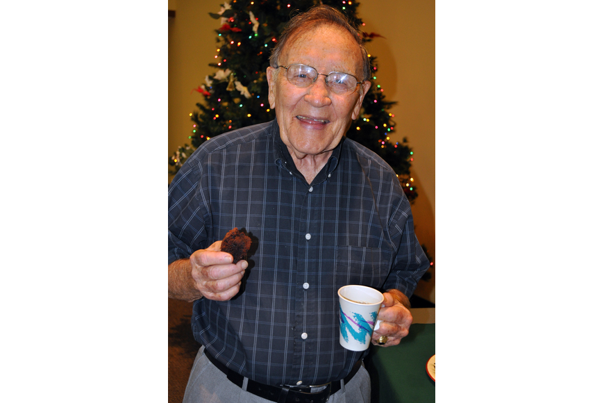 Don Harvey has himself some coffee and a sweet at St. Boniface's annual Cookies and Carols event, Sunday, Dec. 11, inside St. Boniface's Parish Hall.