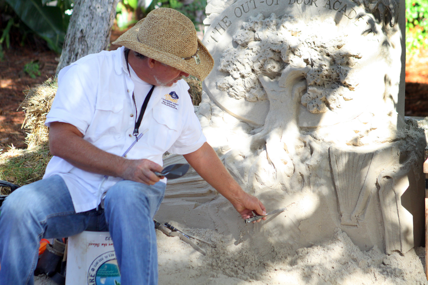 Brian Wigelsworth shows the students how he uses one of his tools to carve into the sand.