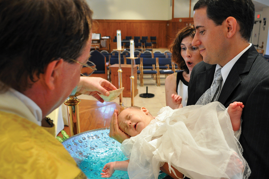 Lori Wolcott gasped while the Rev. Dan TK dumped the first bit of holy water onto her son, Colin Spencer, 6 months, during his baptism in June  at Our Lady of the Angels.