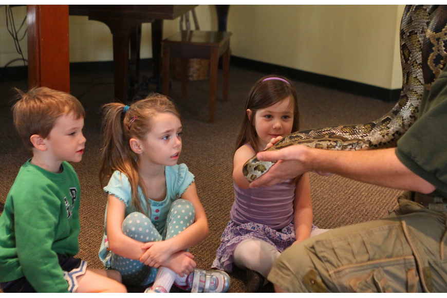 Madilyn Hagney touches Lucky, a Burmese python, as Chance McCarter and Linda Hayes wait their turn, Thursday, Jan. 12, inside the Parish Hall at St. Boniface.