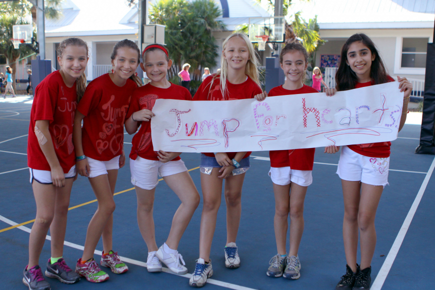 Natasha LaLiberty, 12, Hannah Bizick, 11, Gracie Schlotthauer, 10, Caroline Lafor, 10, Sydney Hill, 10, and Chelsea Lea, 9, pose together with their banner and matching t-shirts.