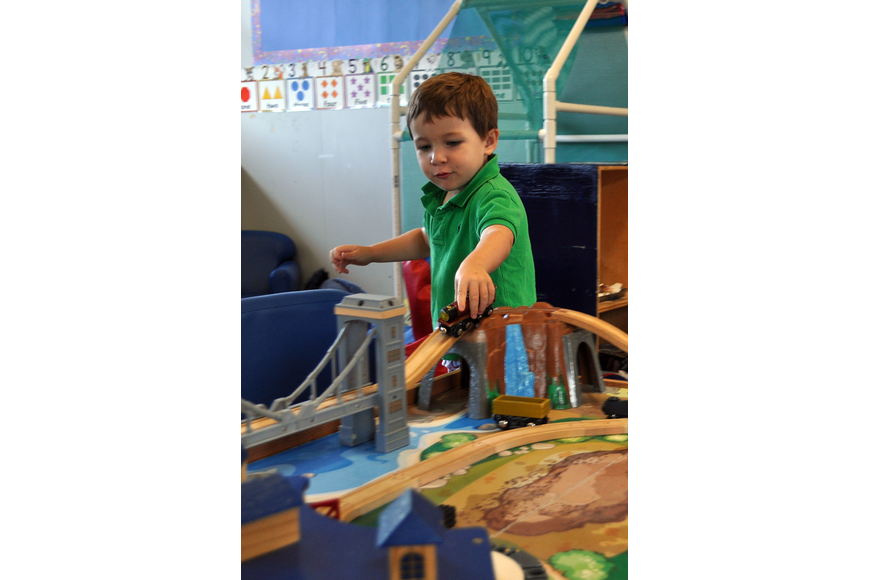 Cooper NaDell plays with the train set in the Dolphin classroom, Monday, Aug. 20.