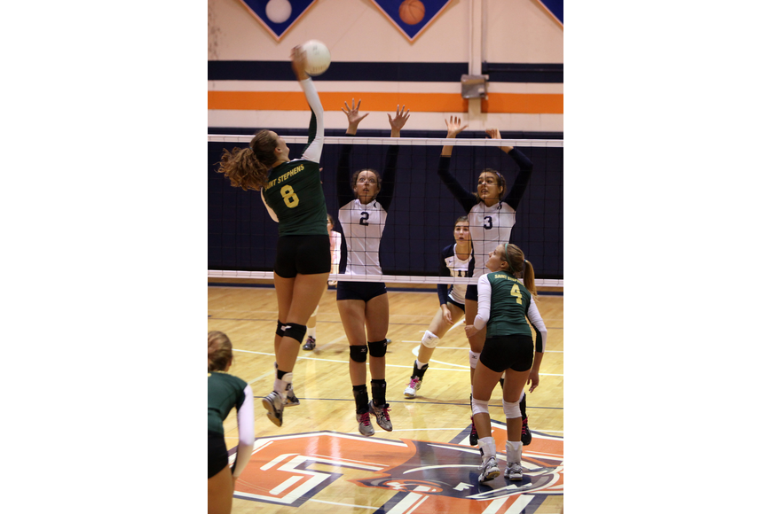 Tori Biach, No. 8, hits the ball as Hailey Preininger, No. 2, and Gabriella Costa, No. 3, prepare to block Biach's shot.
