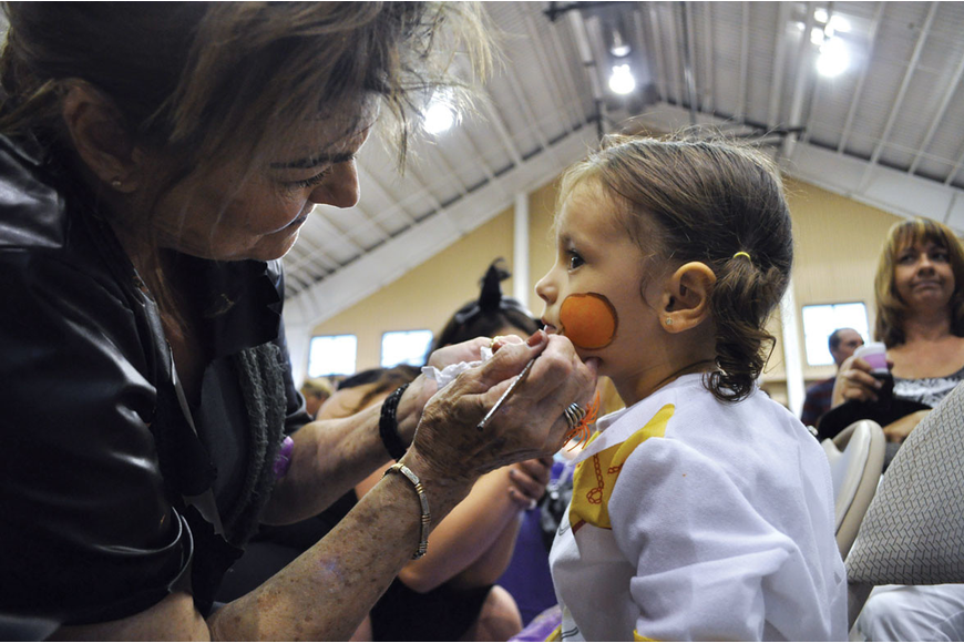 Marge Wallick puts the finishing touches on the face of Aleigha Quiroz, 2, during the YMCA's Family Fall Festival Oct. 19. Published Oct. 25, 2012.