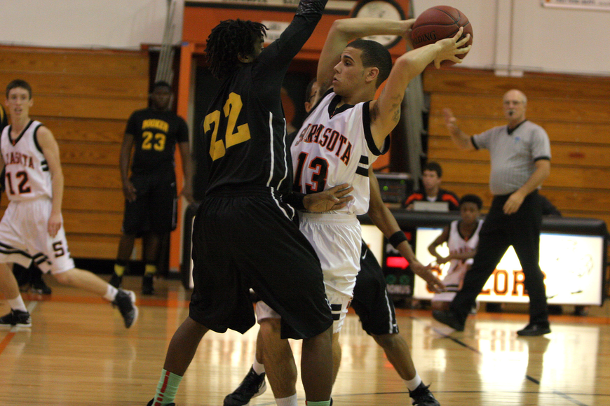 Sarasota High School's Justin Robbins, No. 13, looks to pass to one of his teammates while being guard by Booker High School's Rashad Jones, No. 22.