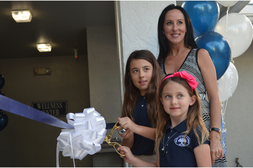 Lexie and Gabby Kozel cut the ribbon to the new Wellness Center as their mother Ashley watches.