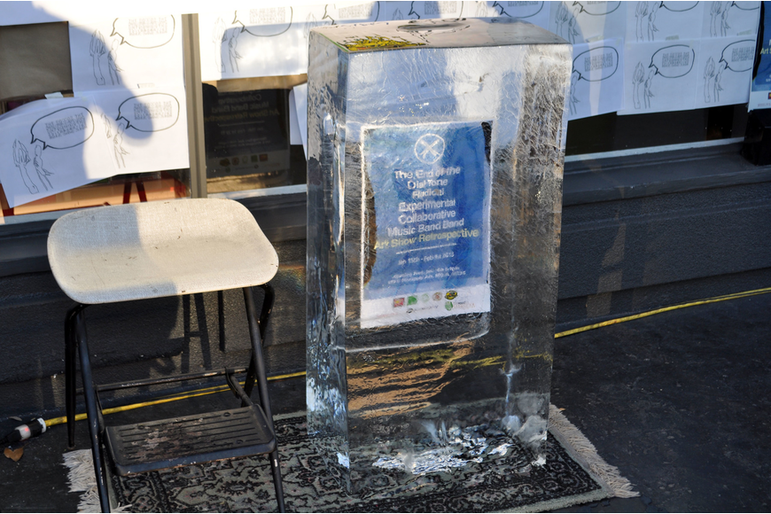 A poster for the event sits frozen inside a block of ice.