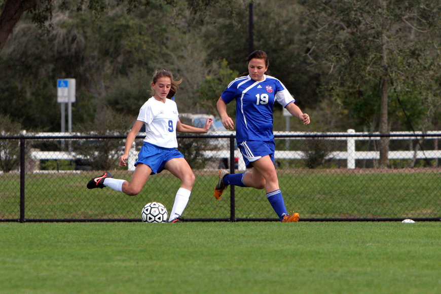Sarasota Christian's Taylor Smith, No. 9, kicks the ball down the field for a pass as Northside Christian's Sydnee Burtzlaff, No. 19, tries to block the pass.