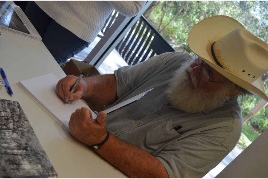 Photographer Clyde Butcher signs his book for those who attended the conference.