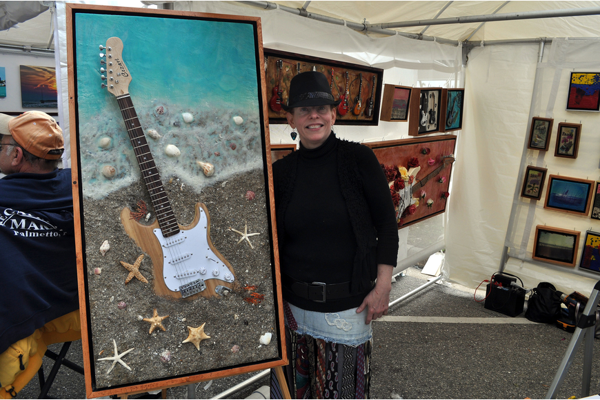 "Jennifer Martin of Mi Corazon Art poses with one of her pieces entitled ""Beach Guitar""."
