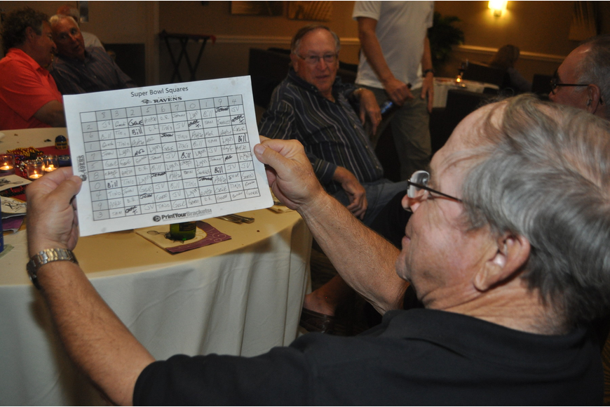 Jim Viera consults the Longboat Key Club Super Bowl point spread sheet.