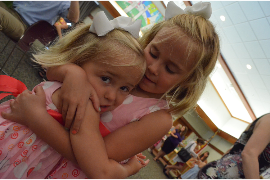 Emerson Miller gives her little sister Elle a hug at the Butterfly Ball.