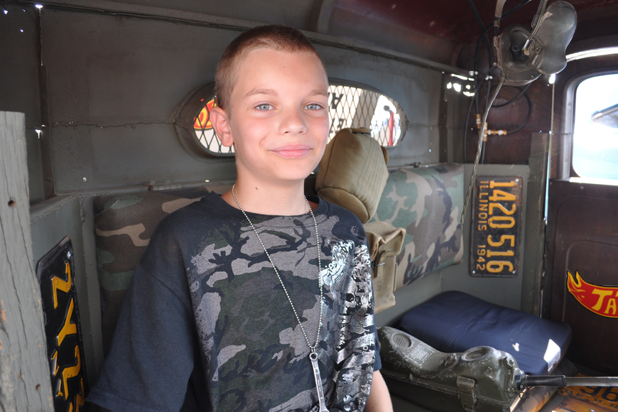 Deacon Marcus, 10, rested in the shade of the '34 international rat rod his father, Matt, built to honor the military.