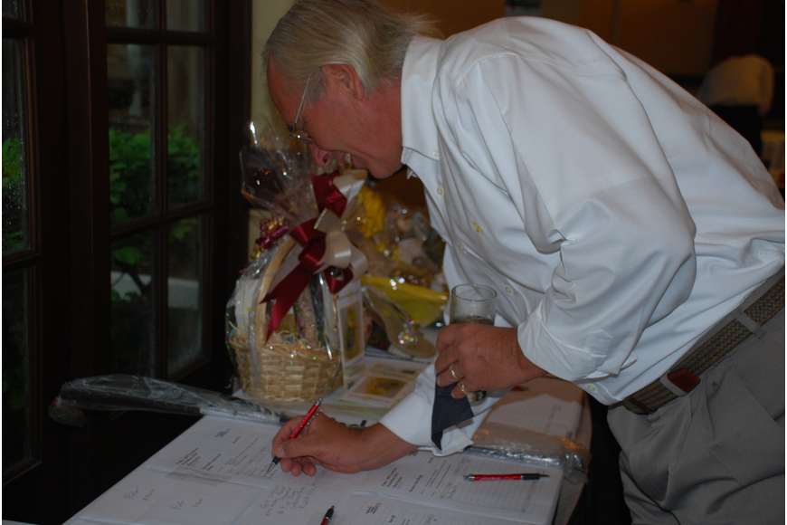 Russ Townsend places a bid on a wine basket in the silent auction