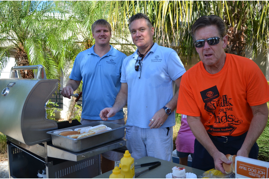 Phillip Hall, Ray Smith and Mike Doyle grill hot dogs for the event.
