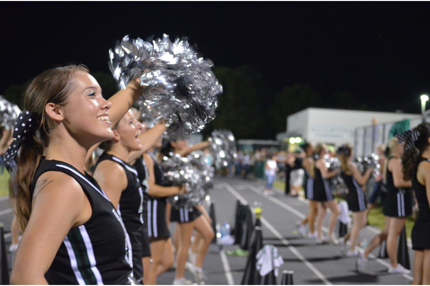 Junior Tiffany Buff, 16, energizes the crowd with fellow cheerleaders, Thursday, Oct. 4, at the homecoming game.