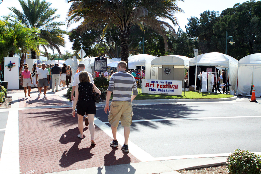 People cross the street to make their way over to St. Armands Circle to attend the 21st annual St. Armands Art Festival.