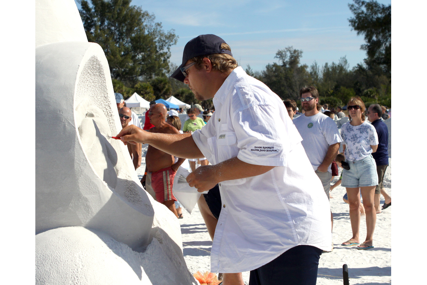 Sandis Kondrats does some detail work on his sand sculpture.