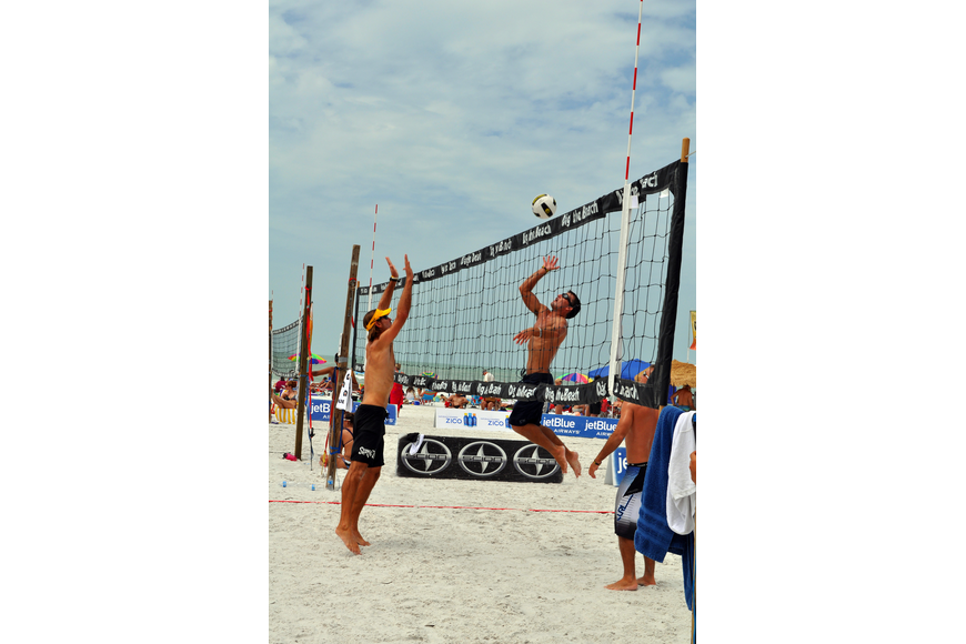 Chris Sweat gets ready to spike the ball while Steve Grotowski prepares to block the ball Saturday, July 9 at Siesta Key Beach.