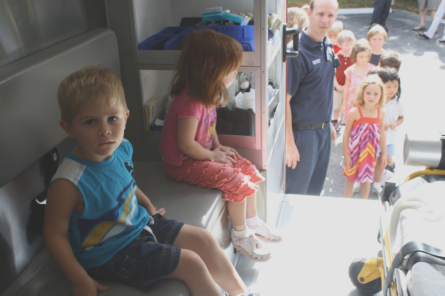 Andre Hersom and Natasha Antoniuk take their turn inside of the ambulance. The rest of the students at St. Boniface Preschool wait their turn in line behind Paul Leverone.
