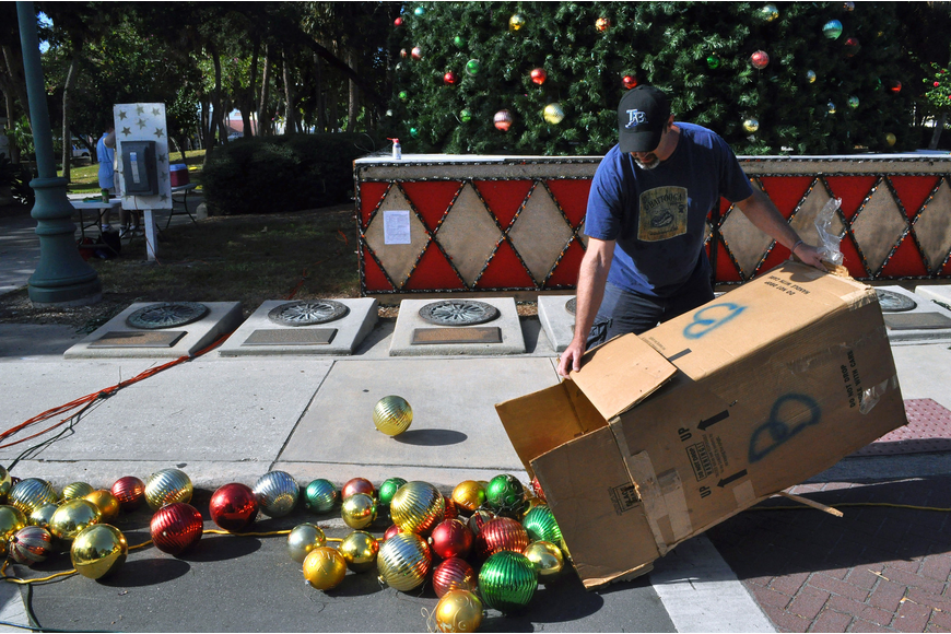 Mike Peffley spills out one of the many large cardboard boxes filled with ornaments onto the street during the tree decorating, Saturday, Nov. 19, out on the circle.