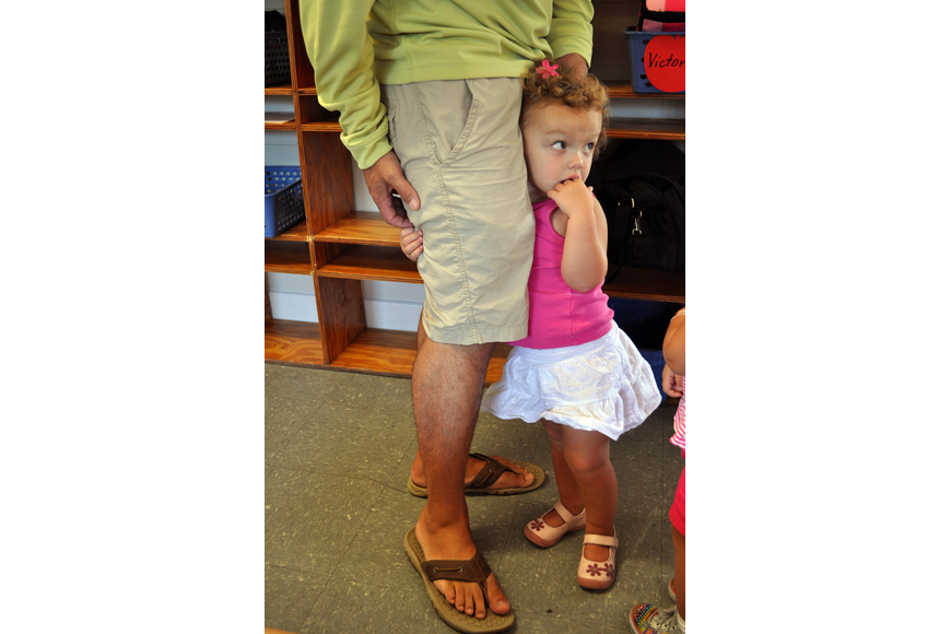 Keira Pritchett, 2, clings to her dad's, Josh, leg on the morning of the first day of school at St. Boniface Preschool.
