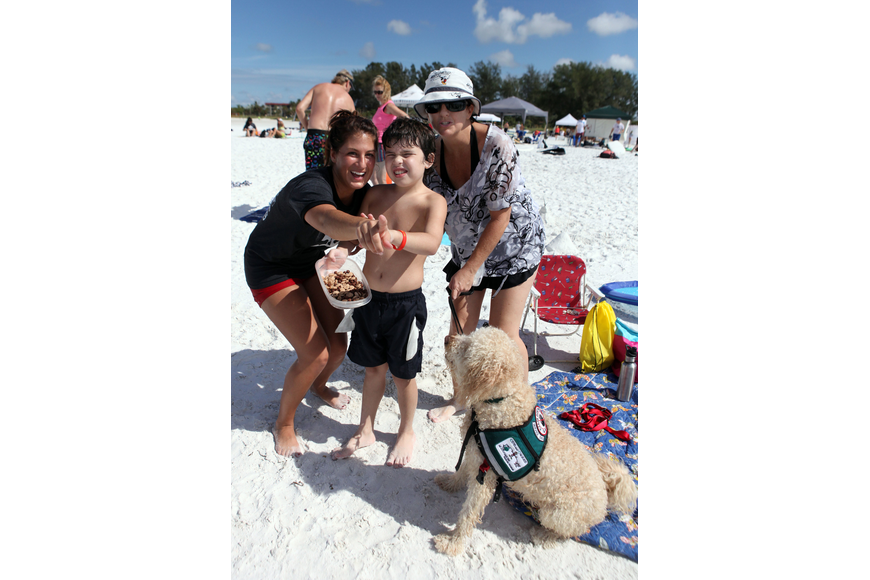 Sion Shipley, Max Whittemore, 10, Marla Whittemore and Luca pose on the beach Saturday, Sept. 15, during Hang 10 for Autism.
