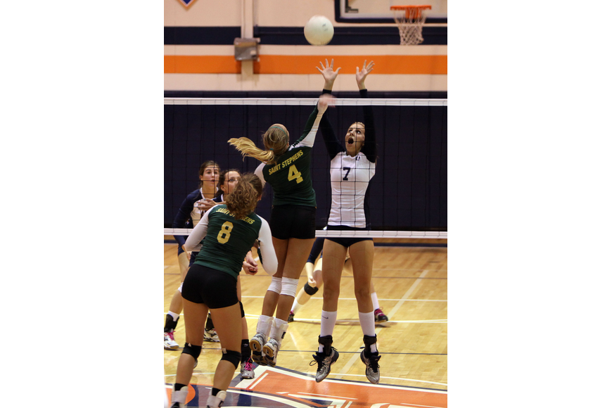 Gabriella Woodruff, No. 4, gets the ball over the net and Emily Greenwood, No. 7, attempts to block Woodruff's shot.