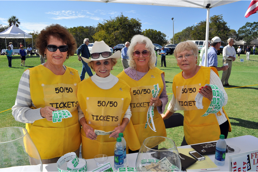 Gosette Whiteneck, Edith Barr Dunn, Susan Randall and Norah Browne pose together in their bright yellow 50/50 raffle outfits.