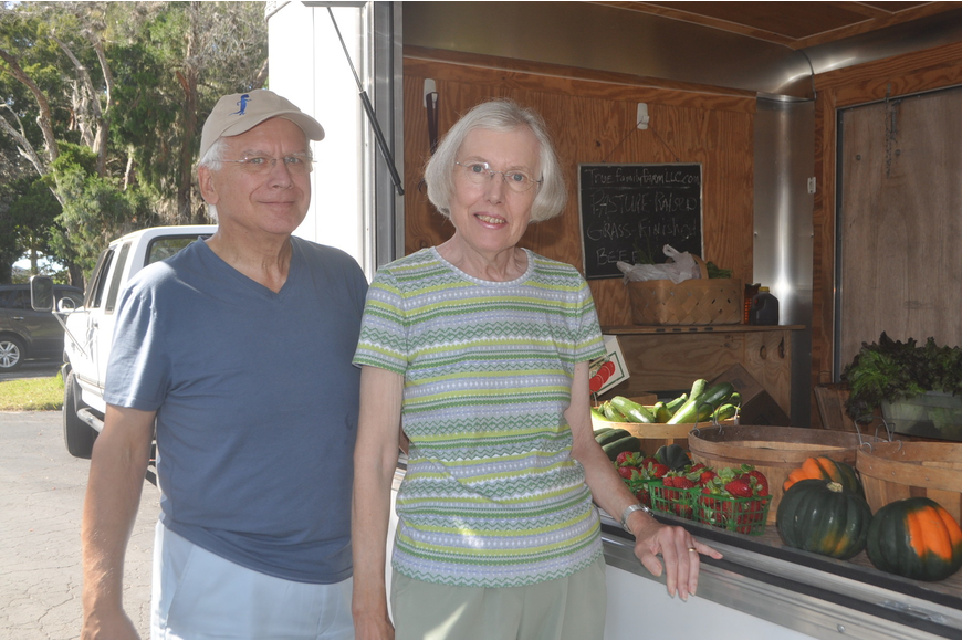 Chet and Linda Pletzke purchase some strawberries, eggplant and tomatoes from Parrish-based True Family Farm's mobile stand.