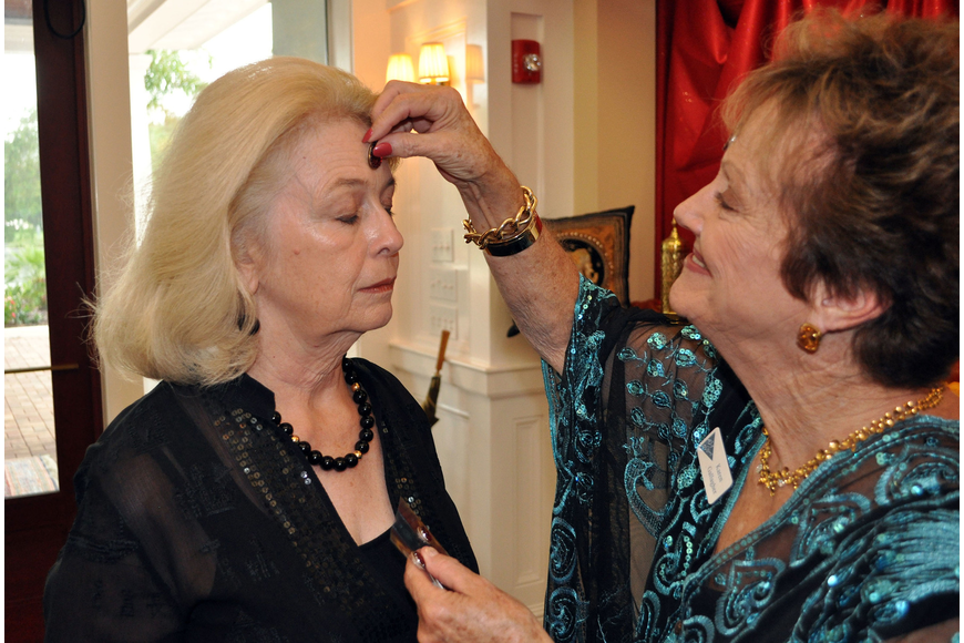 Karen Gallagher applied a bindi, which represents the third eye of wisdom, to Jean Lexton's forehead during an Indian-themed party July 21 at the Bird Key Yacht Club.