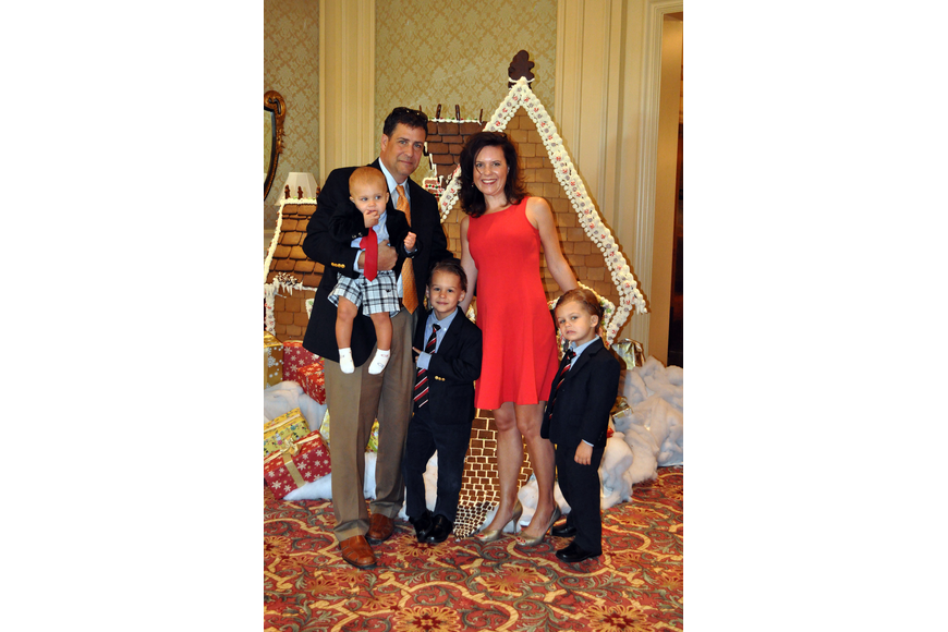 Doug and Shari Phillips pose in front of the large gingerbread house with their sons Parker, 1, Johnathon, 5, and Harrison, 4, Sunday, Dec. 16, at the Breakfast with Santa event at the Ritz Carlton.