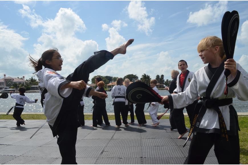 Cassidy Lawless, 9, holds up kicking pads for Amber Riggs, 11. They are both students at Mingwu Martial Arts.