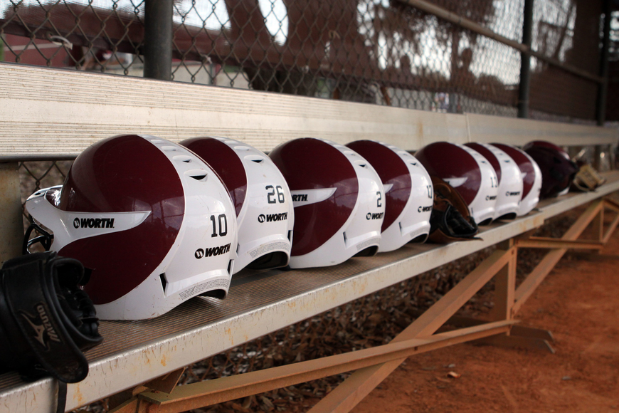Riverview's helmets all lined up on the bench inside Riverview's dugout.