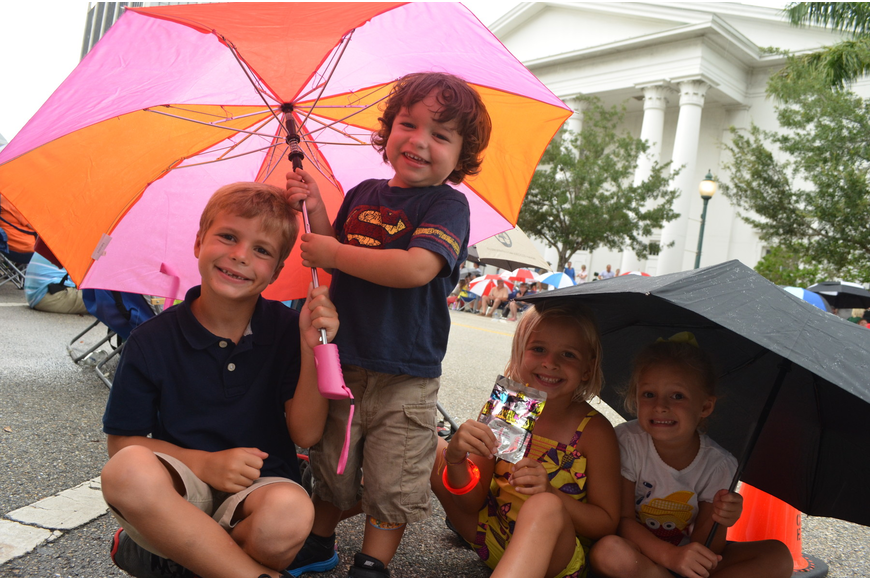 Landon Marsters, 6, Dylan Carrillo, 2, Tegan Hoffman, 5, and Madelyn Marsters, 4, hide underneath umbrellas as the rain begins at the start of the parade.