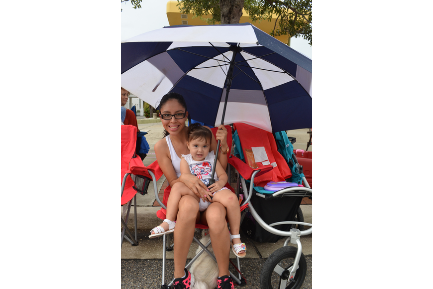 Monika Burke and her daughter Penny, 2, hide under an umbrella during the parade.
