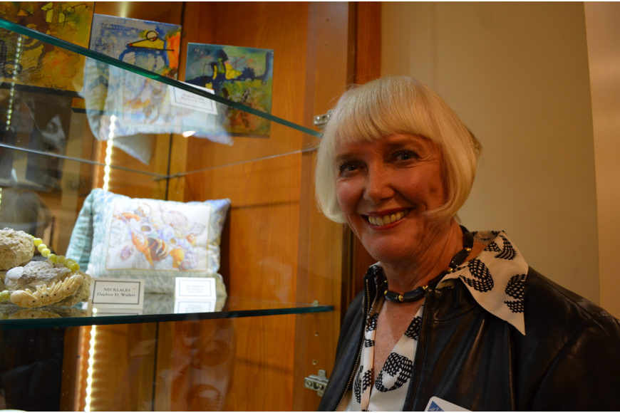 Exhibitor Anita Pihl in front of her needlepoint pillow