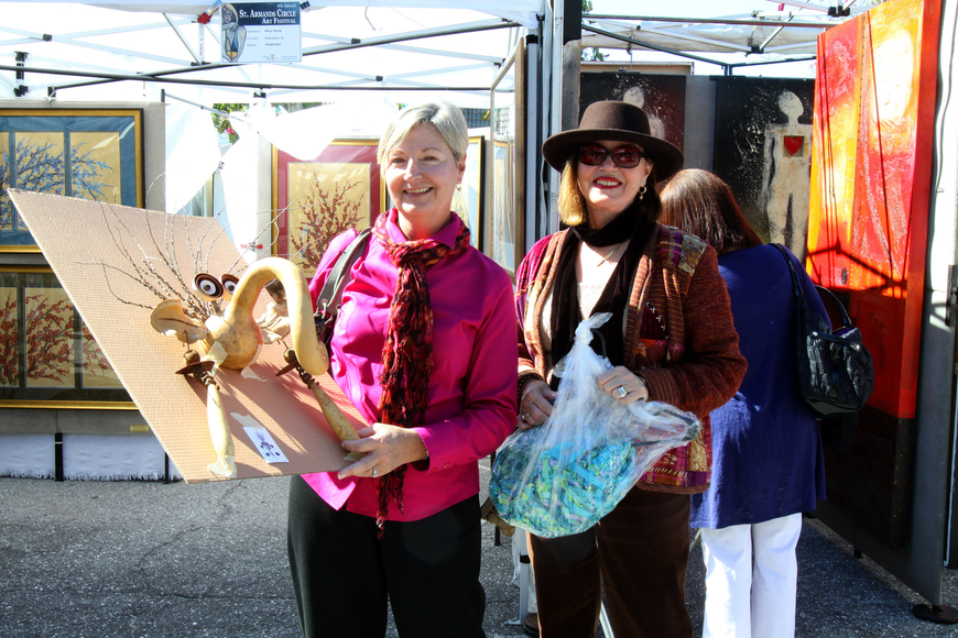 Janice Cook and Linda Zuczek show what they bought on Saturday, Jan. 29 at St. Armand's Art Fair.