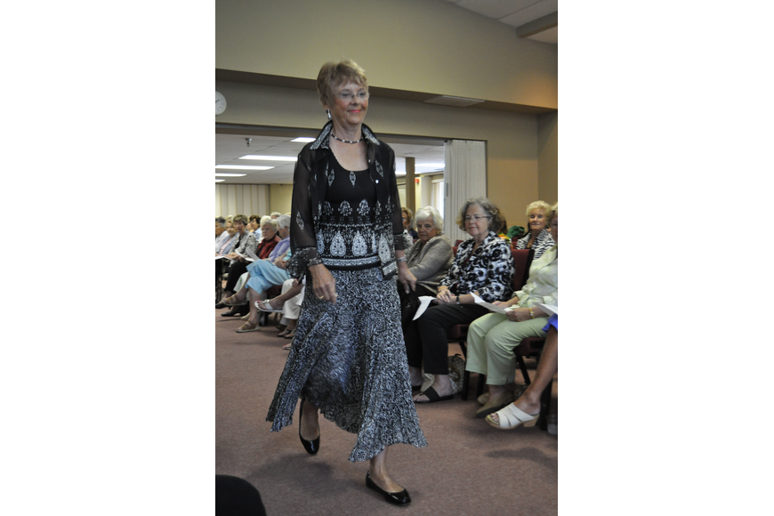 Beth Rumble walks the runway in a flowy printed skirt and matching top.