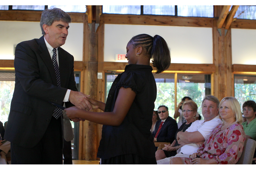 Kiarra Womack shakes hands with Headmaster Mahler while receiving the Citizen of the Year award.