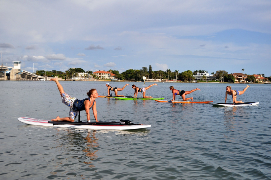 Michelle Young, Christina Zash, Lynne Orlando and Nina Schmidt follow Ami French during a yoga paddle boarding class, Thursday, June 23 out at New Pass Park.