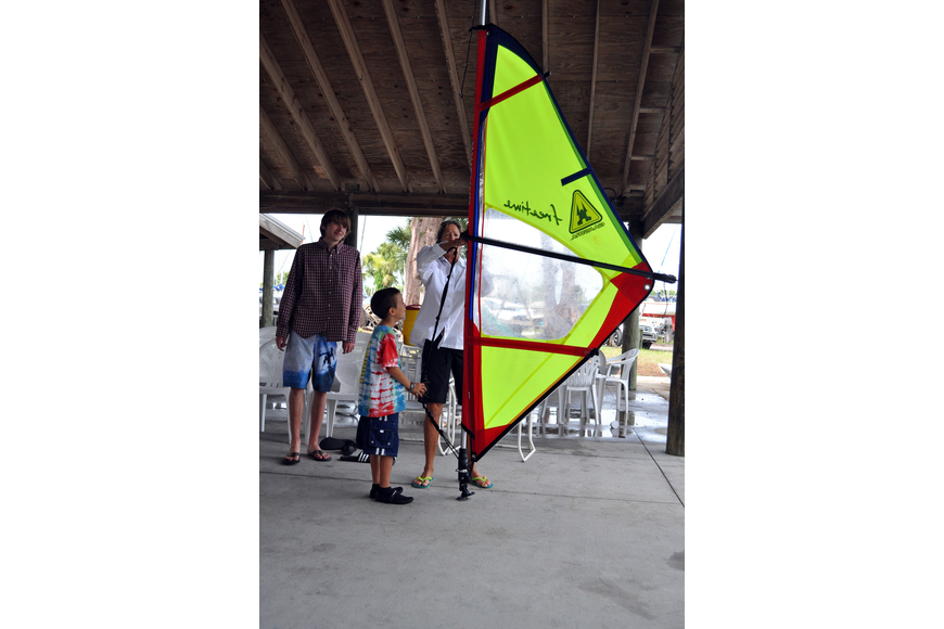 Laurel Kaiser tries to make the sail the right size for Jeffrey Rosenthal, 8, Friday, July 8 during the Island Style Water Sports Camp.