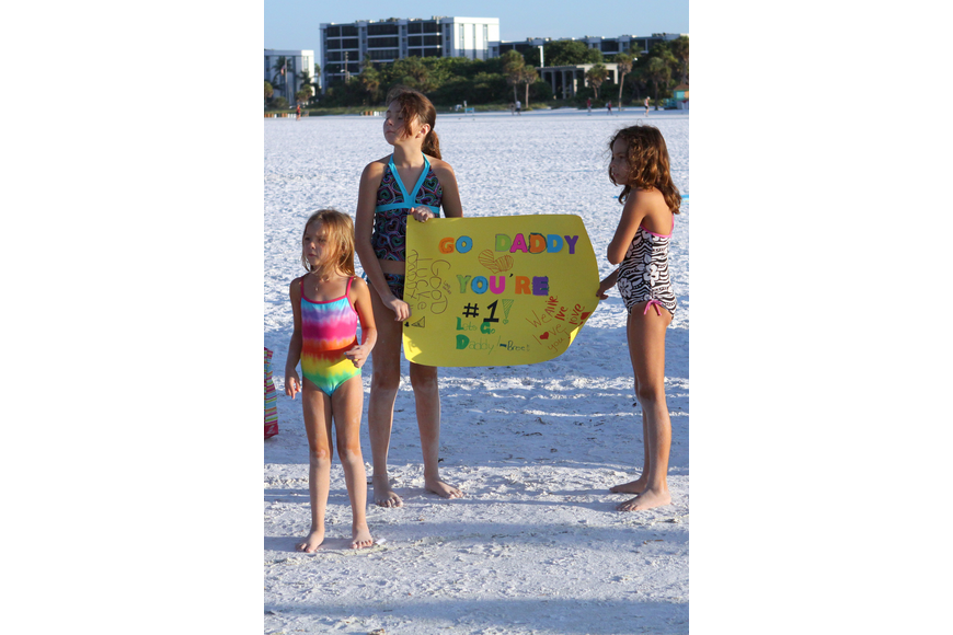 Bree, 10, and Hailey, 8, hold their homemade sign while their younger sister, Allie, 5, Vazquez keeps a look out for their dad, Yamani, Saturday, July 23 during the Siesta Key Triathlon out at Siesta Key Public Beach.